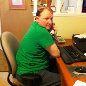 Hubby sitting at his desk in a green t-shirt