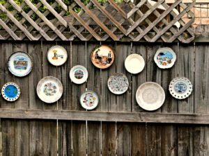 decorative plates hanging on the backyard fence