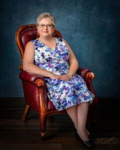 mylifesuchasitis.com elizabeth white 2020 offiical portrait sitting in leather chair. wearing a floral print sundress
